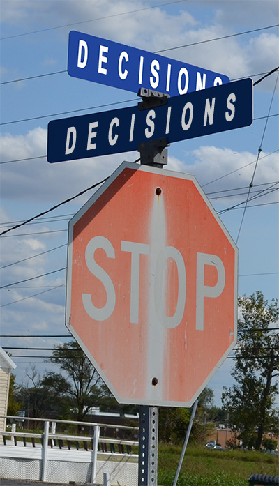 stop sign at the corner of decions and decisions